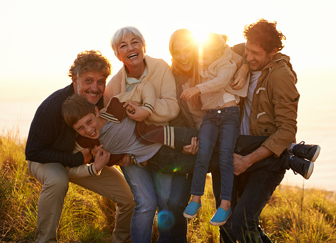 Group of family members hugging and being silly while laughing in the sunlight