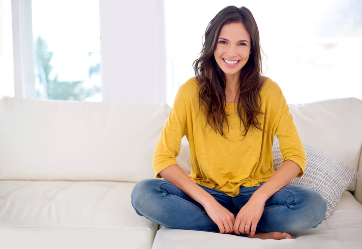 Woman in a bright yellow shirt sitting on a couch and smiling after receiving veneers at 's Phoenix office