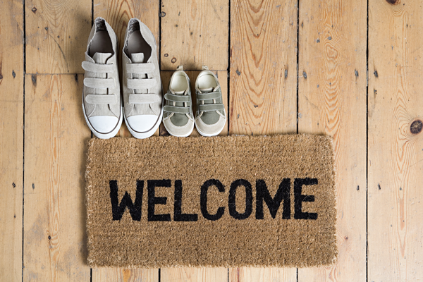 Welcome Mat with two different size shoes next to it